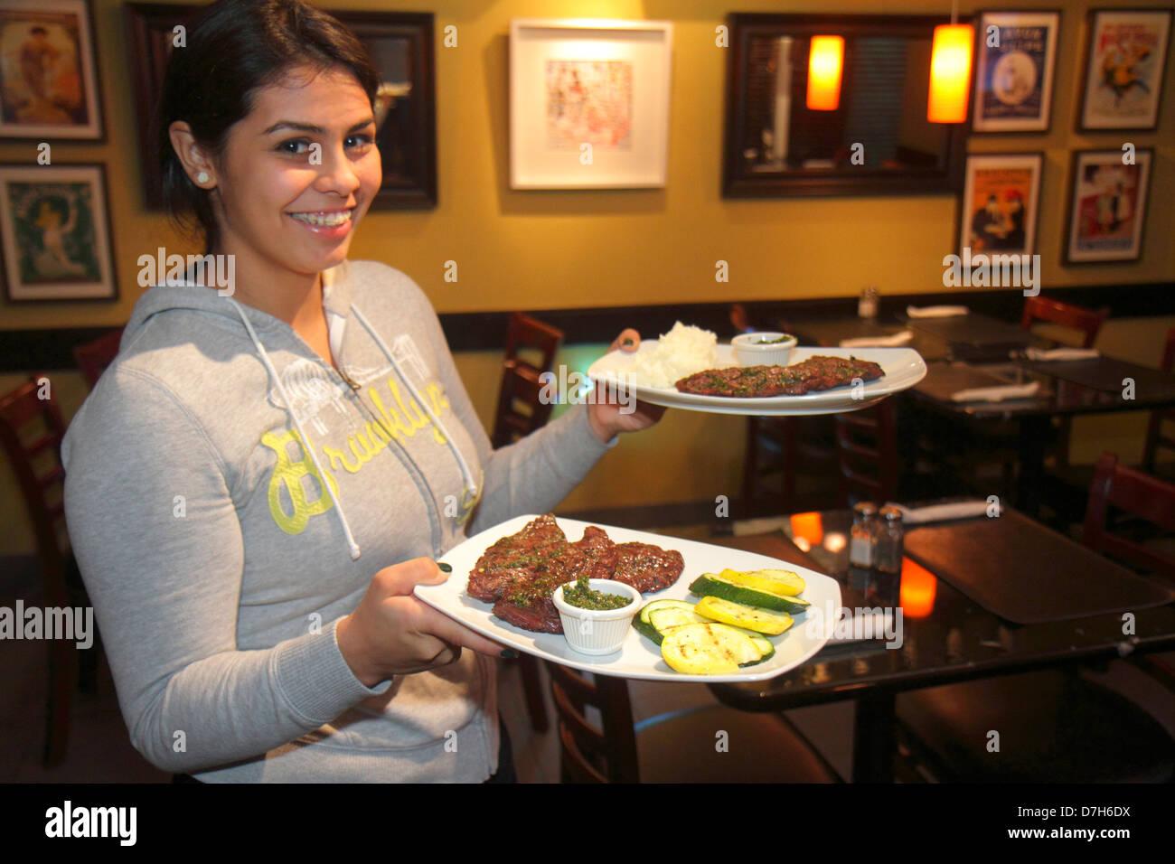 Miami Florida Coral Way 1401 Argentinean Bistro restaurant Hispanic teen girl waitress working job serving plates Stock Photo