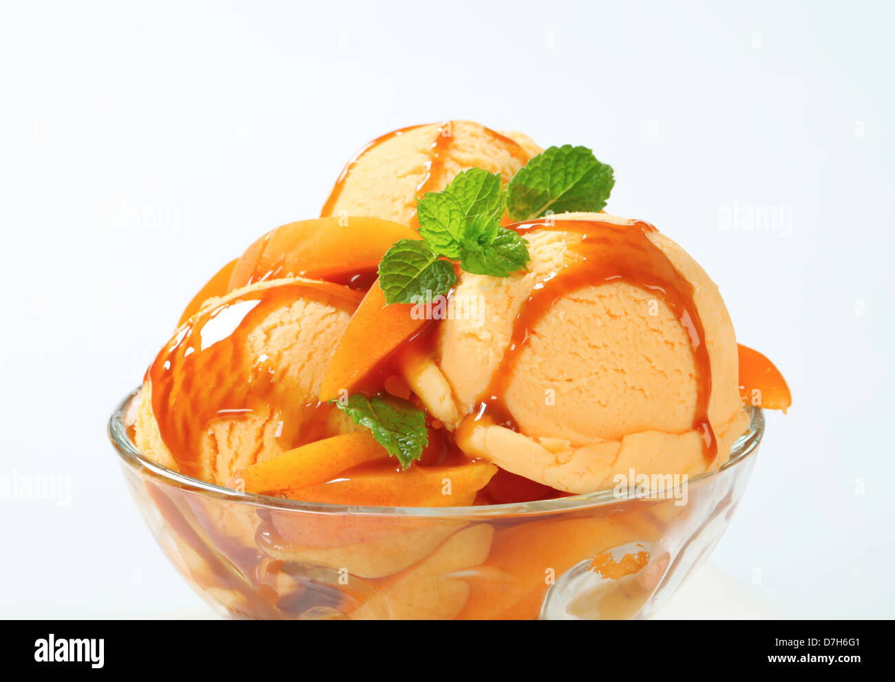 Ice cream with fresh apricot and caramel sauce - Stock Image