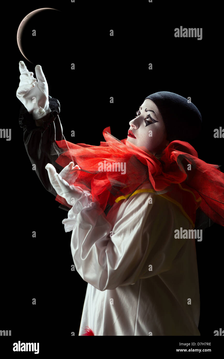 Beautiful Pierrot clown playing mime with the moon - Stock Image