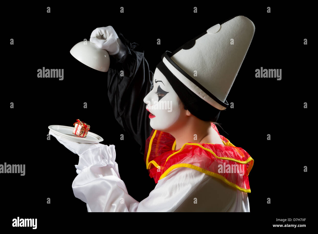 Mime Pierrot actor finding a gift under on a white dish tray - Stock Image
