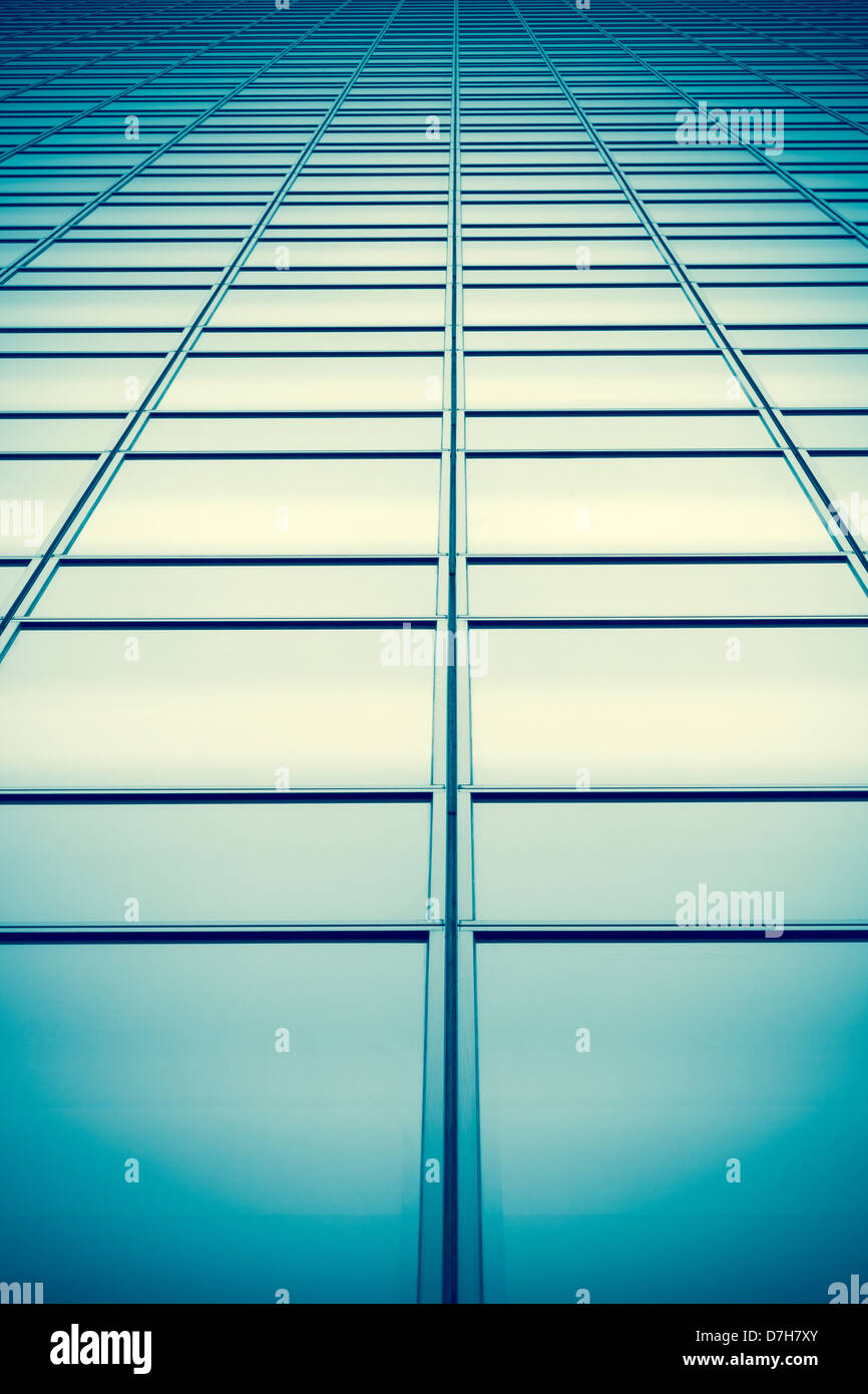 Converging panes of glass windows on a tall building with a cross processed colour treatment. - Stock Image