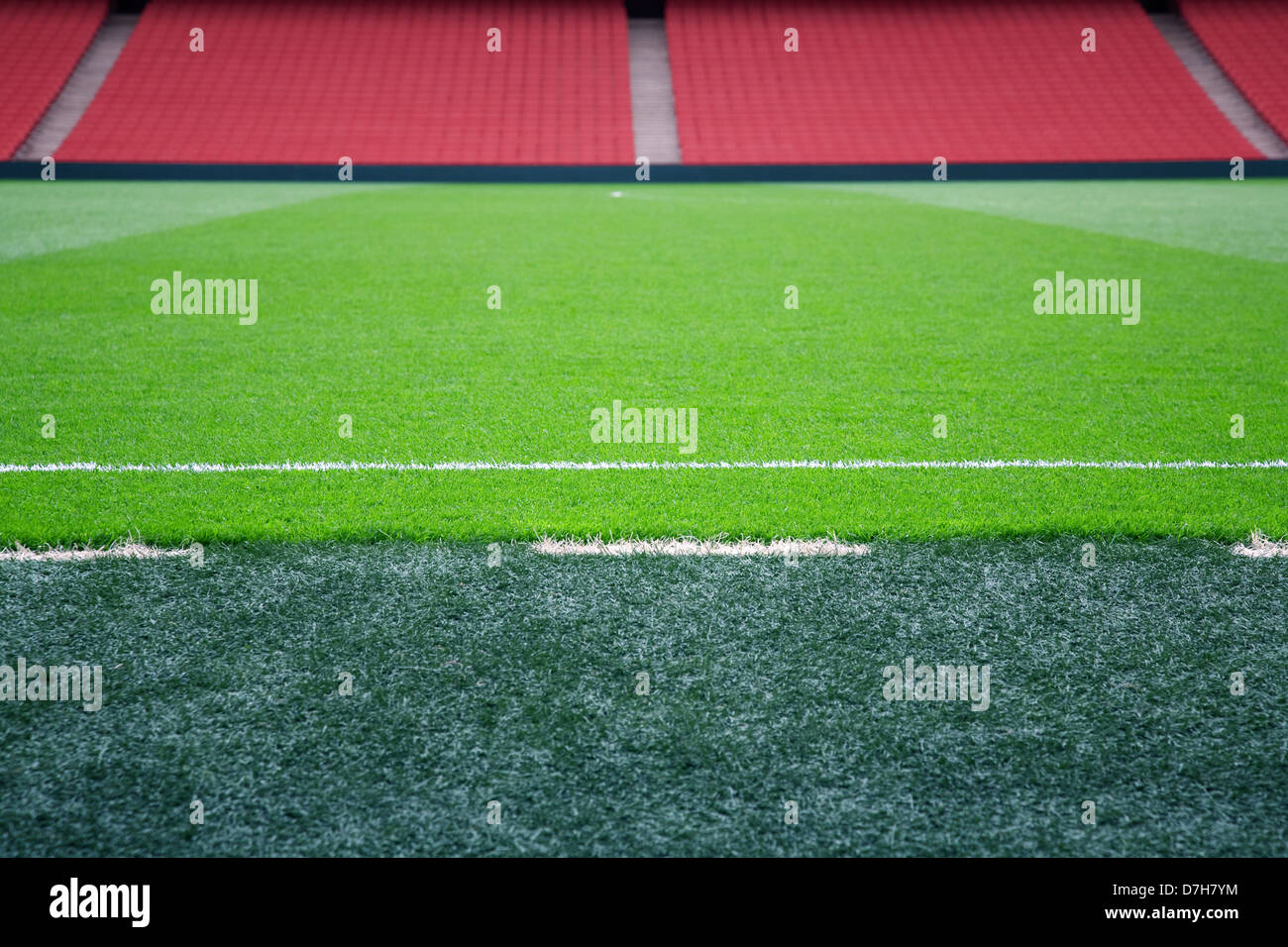 Empty football pitch with red seating, selective focus on touchline. - Stock Image