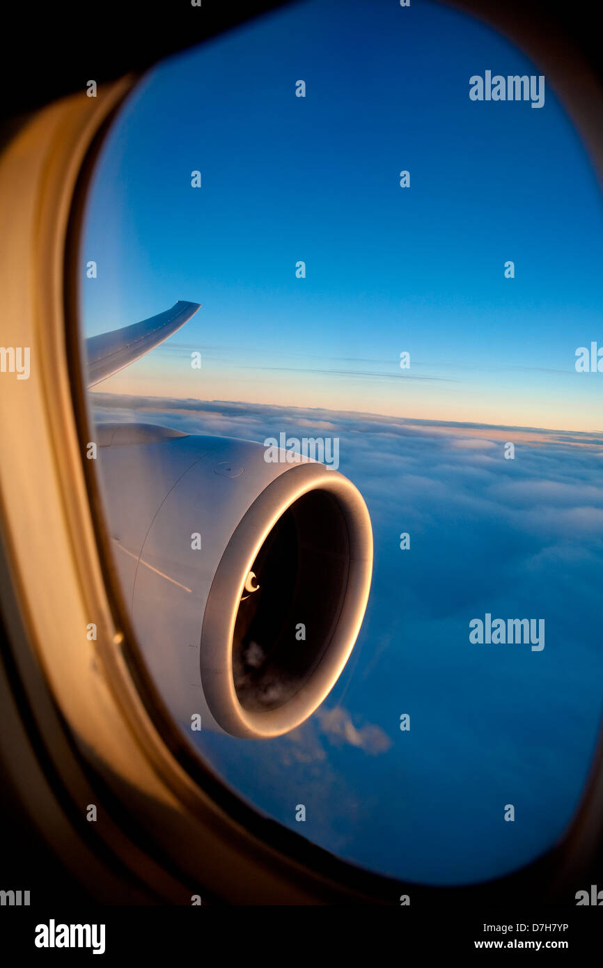 Passenger view through the window of a jet plane showing sky, clouds, jet engine and wing. - Stock Image