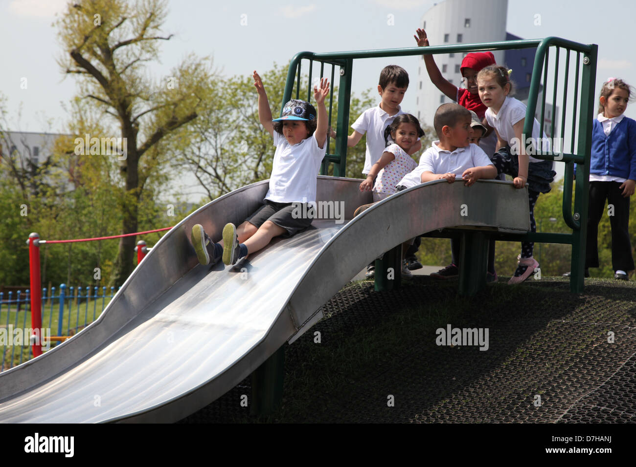 Children playing on a slide in a playground in London - Stock Image