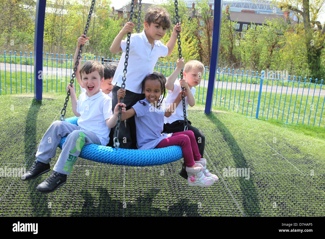 Children playing on a tyre  / tire swing in a London playground. - Stock Image