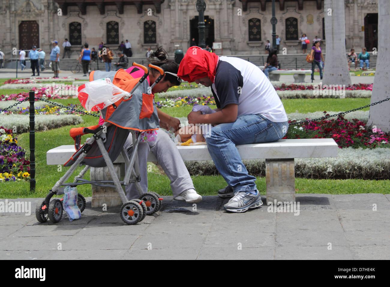 Peru Lima Plaza Mayor or Plaza de Armas parents wrap child wind - Stock Image