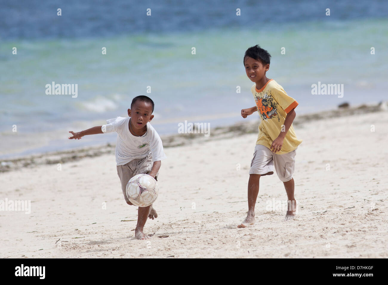 Young local boys playing football on a beach in Boracay, Philippines Stock Photo