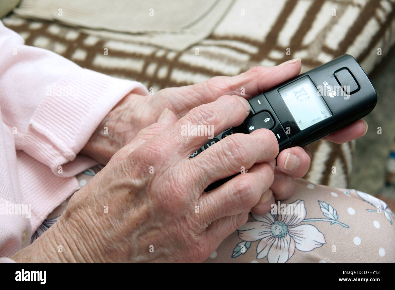 Elderly woman using a specialised big button telephone phoning the 111 non emergency medical advice helpline due Stock Photo
