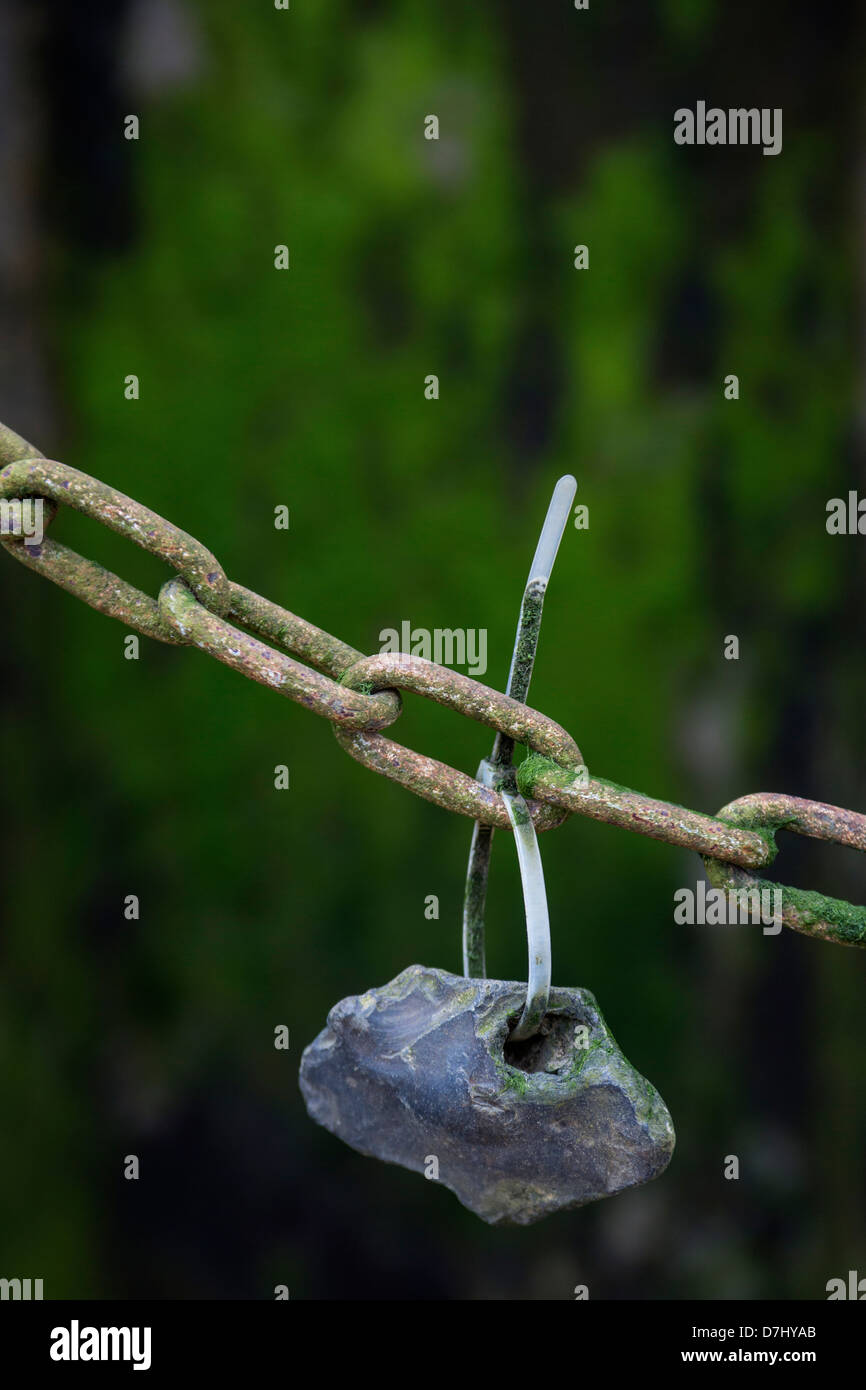 A small stone with a hole in it wire-tied to a rusty chain. - Stock Image