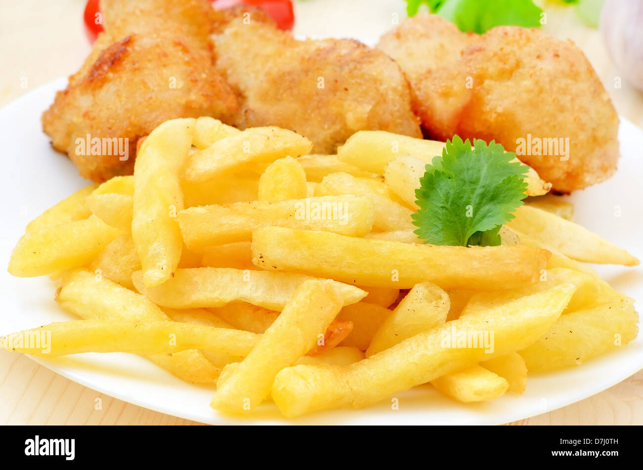French fries with fried chicken on a white plate - Stock Image