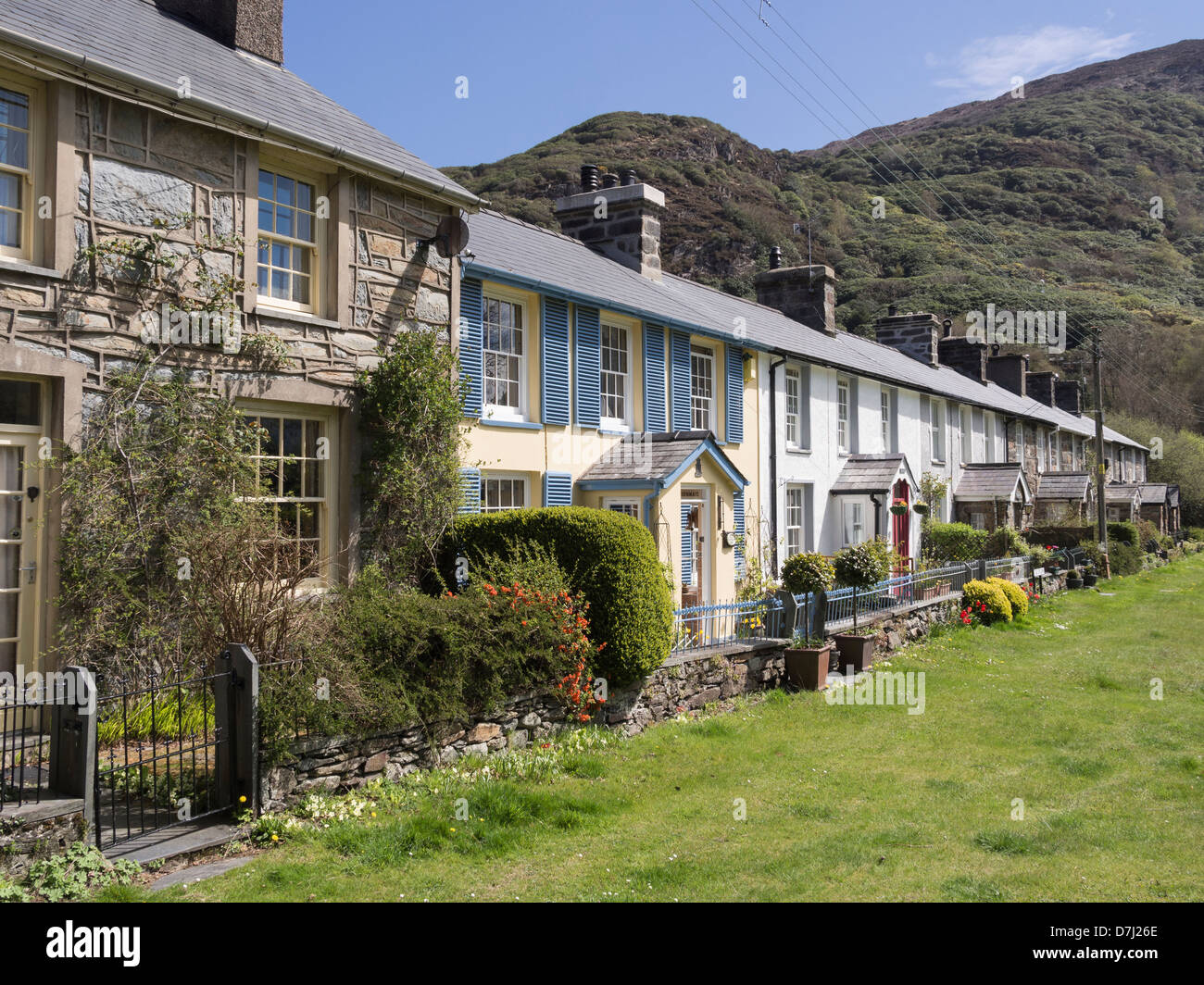 Row of traditional terraced cottages overlooking picturesque Welsh village green in Snowdonia National Park. Beddgelert, - Stock Image