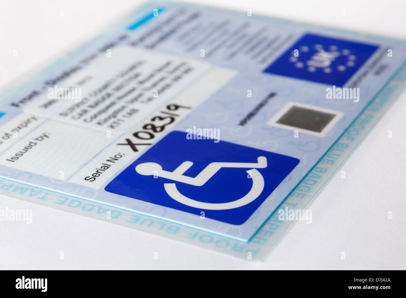 Blue badge card with wheelchair symbol for disabled parking concessions scheme. England, UK, Britain, Europe. - Stock Image