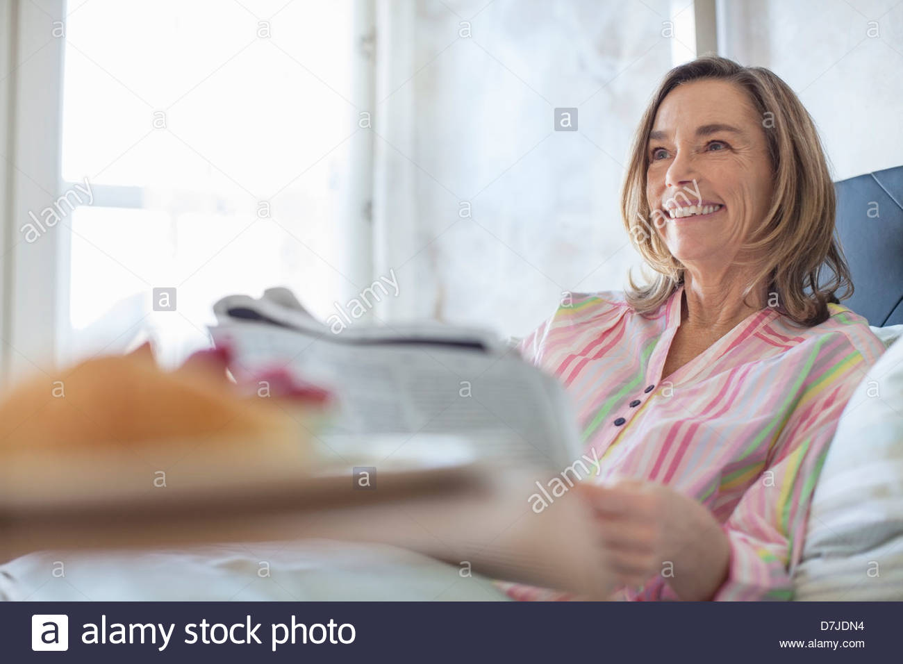 Senior woman reading newspaper in bed Stock Photo