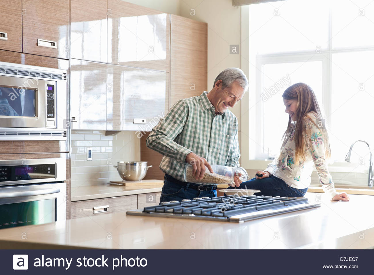 Grandfather preparing breakfast for granddaughter in kitchen - Stock Image