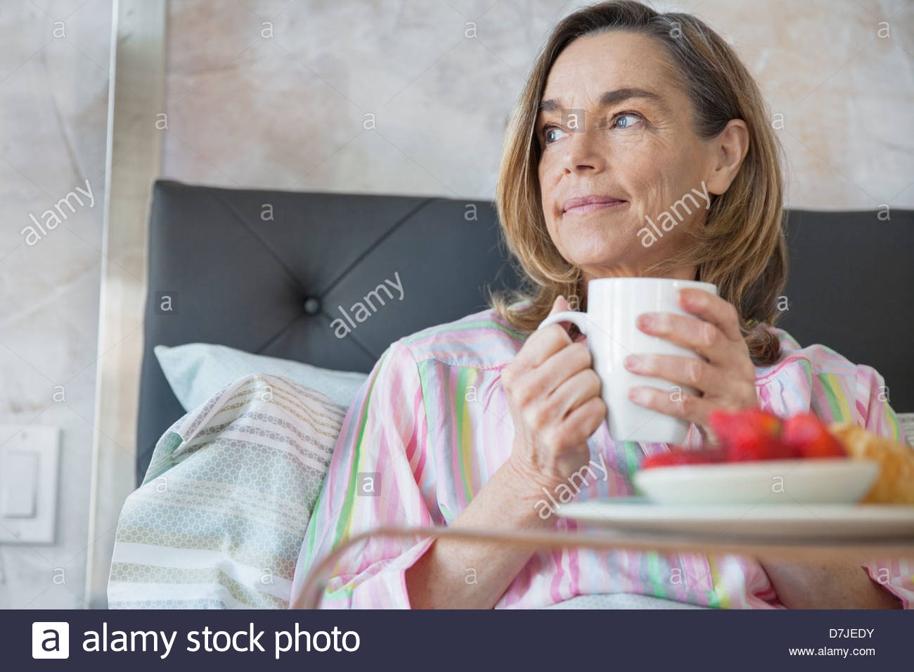 Senior woman having coffee and breakfast in bed - Stock Image