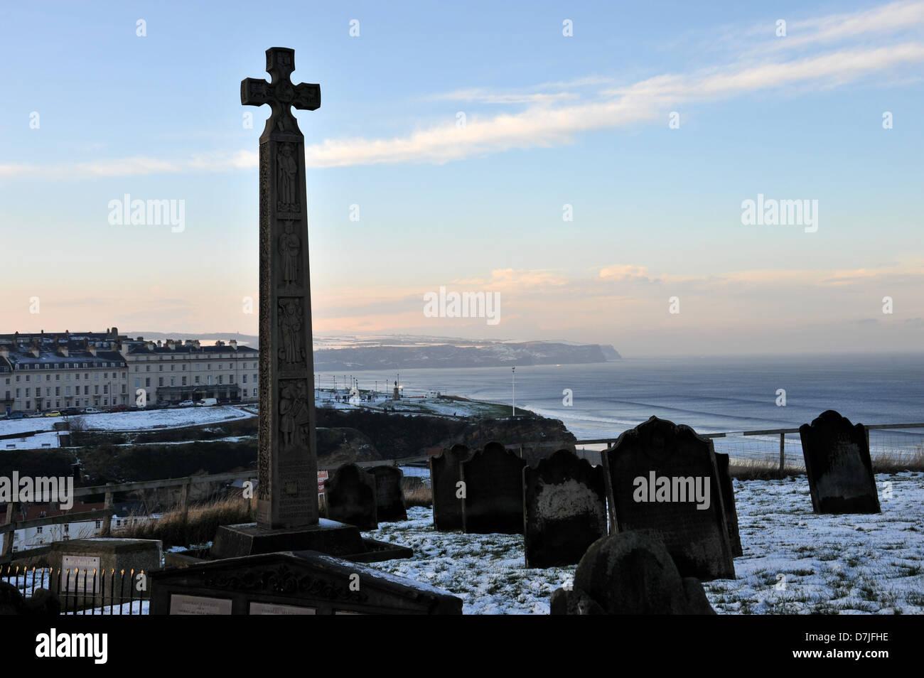 whitby graveyard,cross,wintery scene,cliffs, sea,gravestones,town,coastline,town,north seablue skies,cliffs,snow - Stock Image