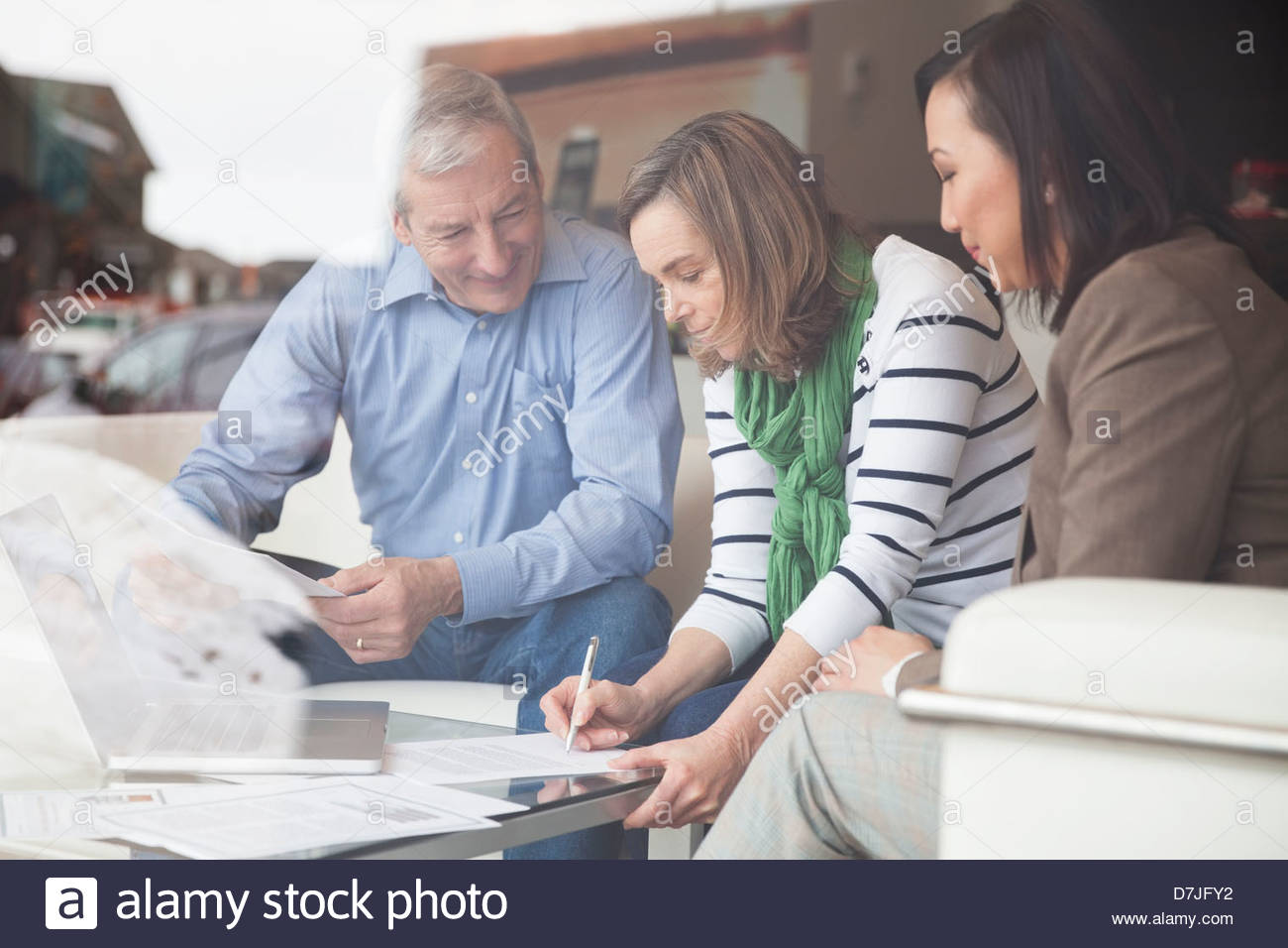 Senior couple signing documents with financial advisor at home - Stock Image