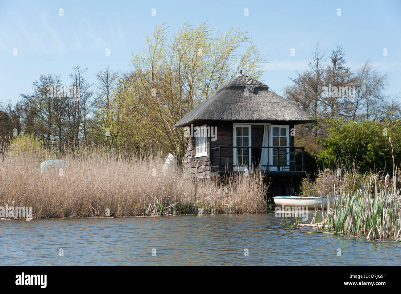 A thatched summerhouse and boat mooring at The Meare Thorpeness near Aldeburgh Suffolk UK - Stock Image