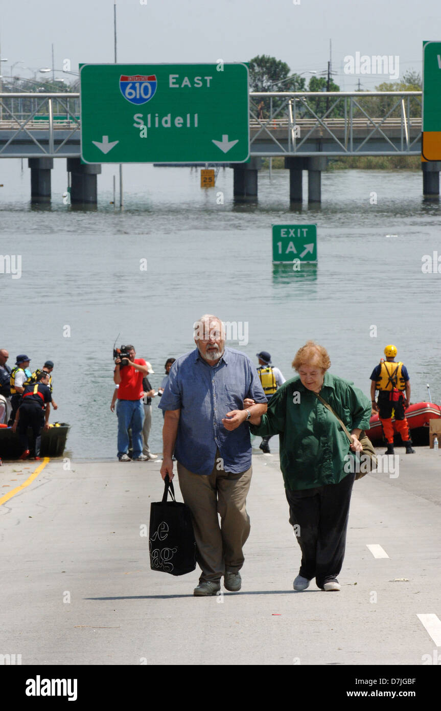 An elderly couple walk up the ramp to the Superdome after being rescued from their flooded home as the city is evacuated - Stock Image