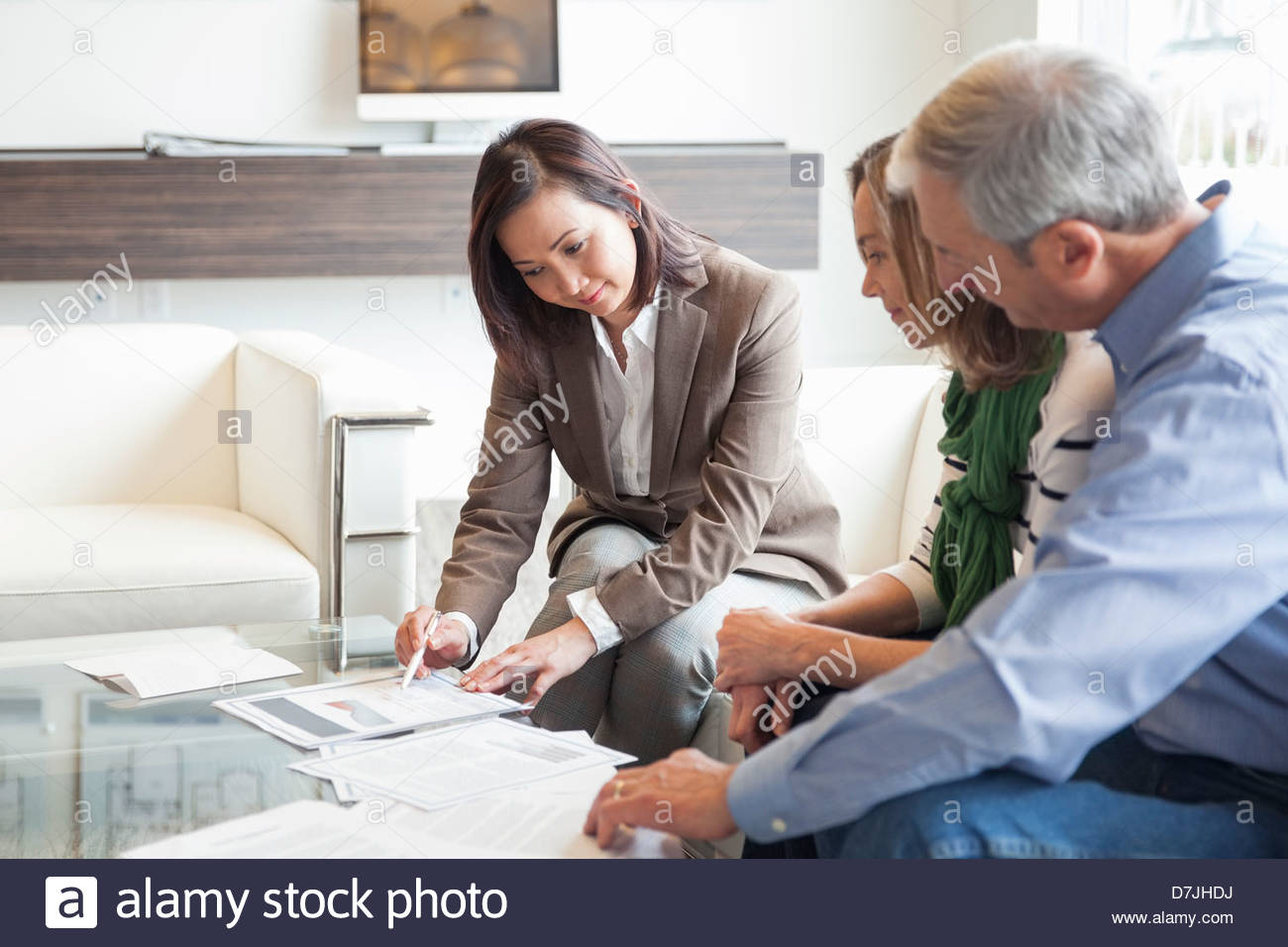 Senior couple getting advice from financial advisor at office - Stock Image