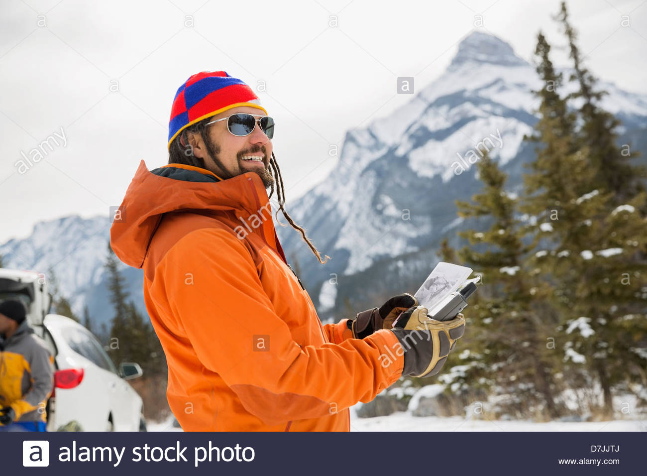Smiling man with map and GPS in mountains - Stock Image