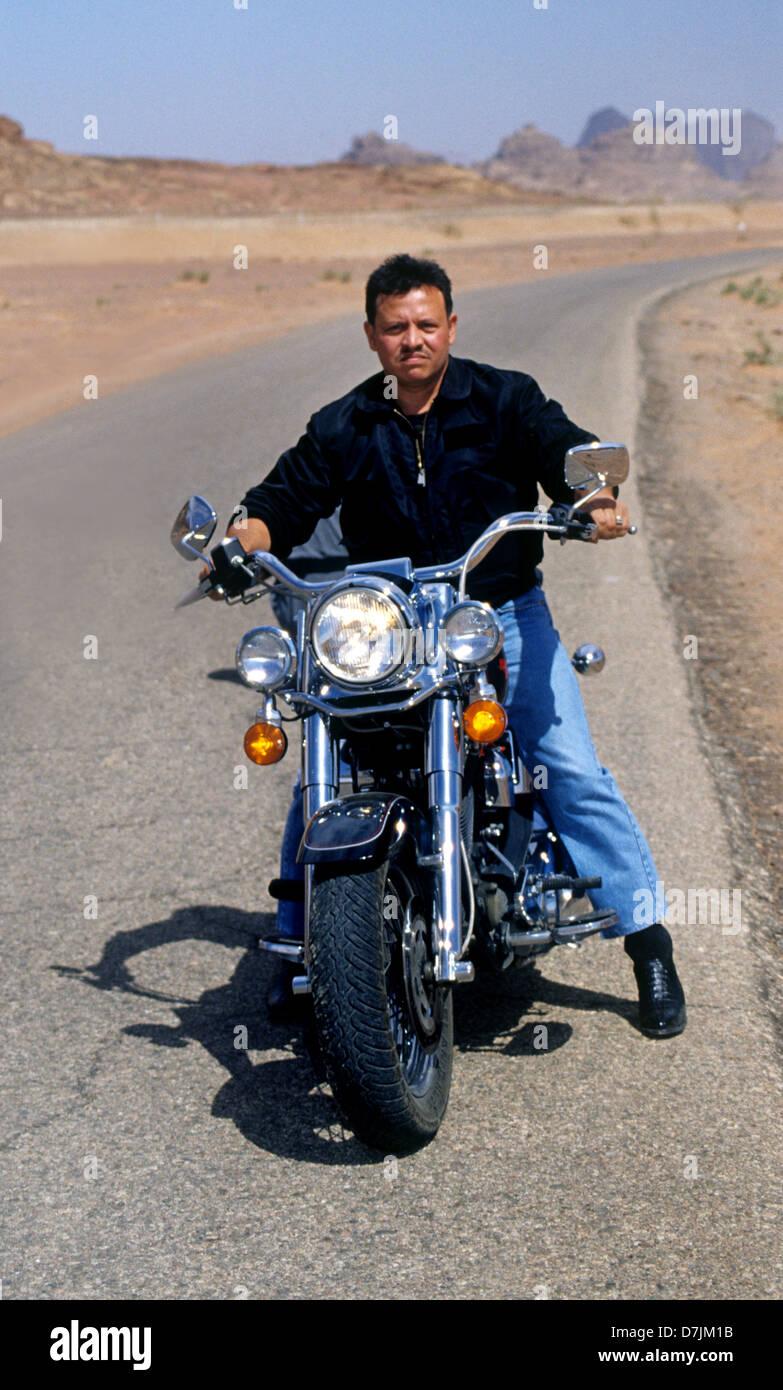 King Abdullah II of Jordan riding his motorcycle in Wadi Rum - Stock Image