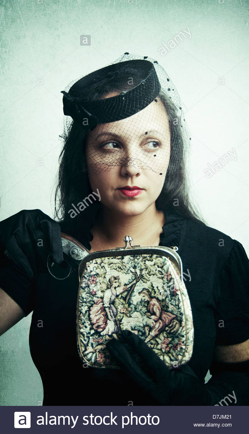 Beautiful woman wearing vintage hat with veil appearing to pull a pistol out of an old vintage purse, mysterious - Stock Image
