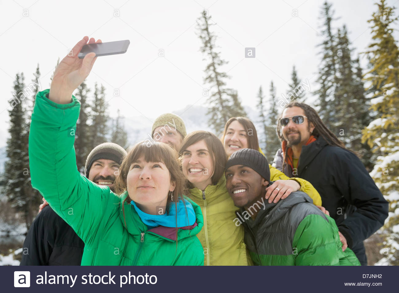 Group of friends taking self portrait with mobile phone in mountains - Stock Image
