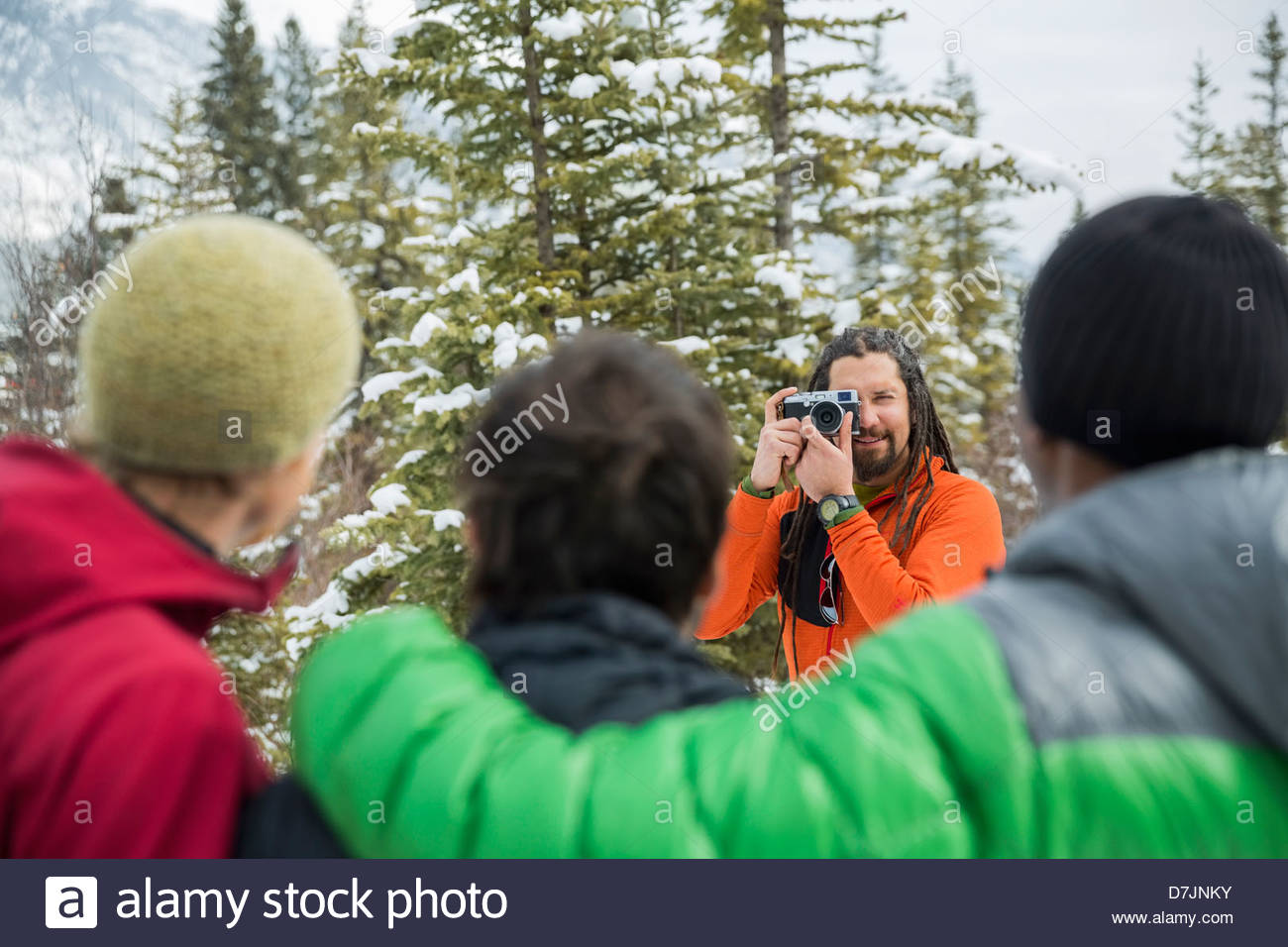 Man taking photograph of friends outside in winter - Stock Image