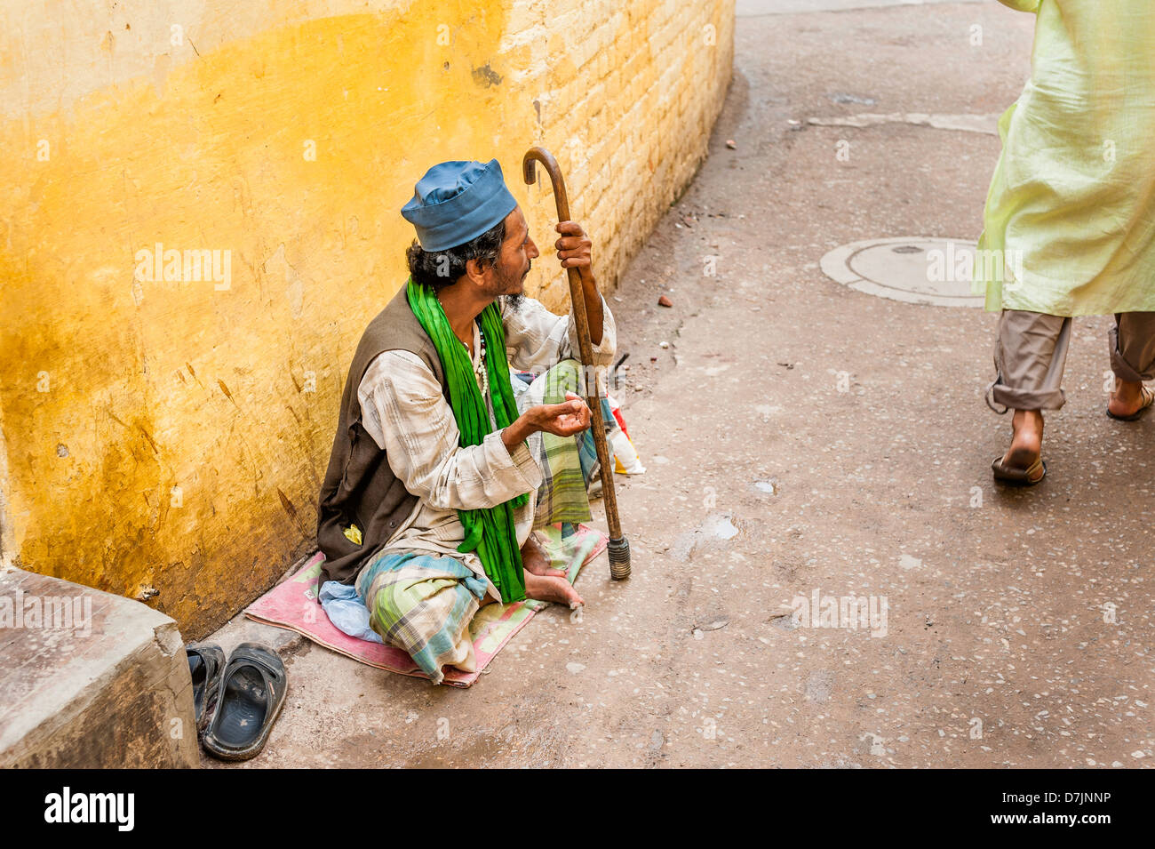 Beggar seeks alms on a narrow street in Nizamuddin, a Muslim suburb of Old Delhi, India. - Stock Image