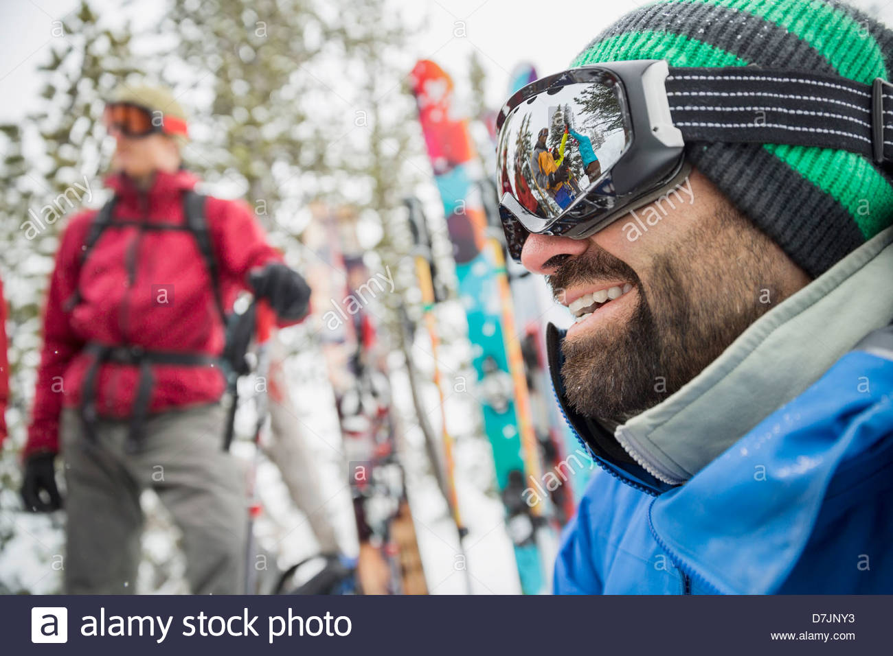 Smiling male backcountry skier with friends in mountains - Stock Image