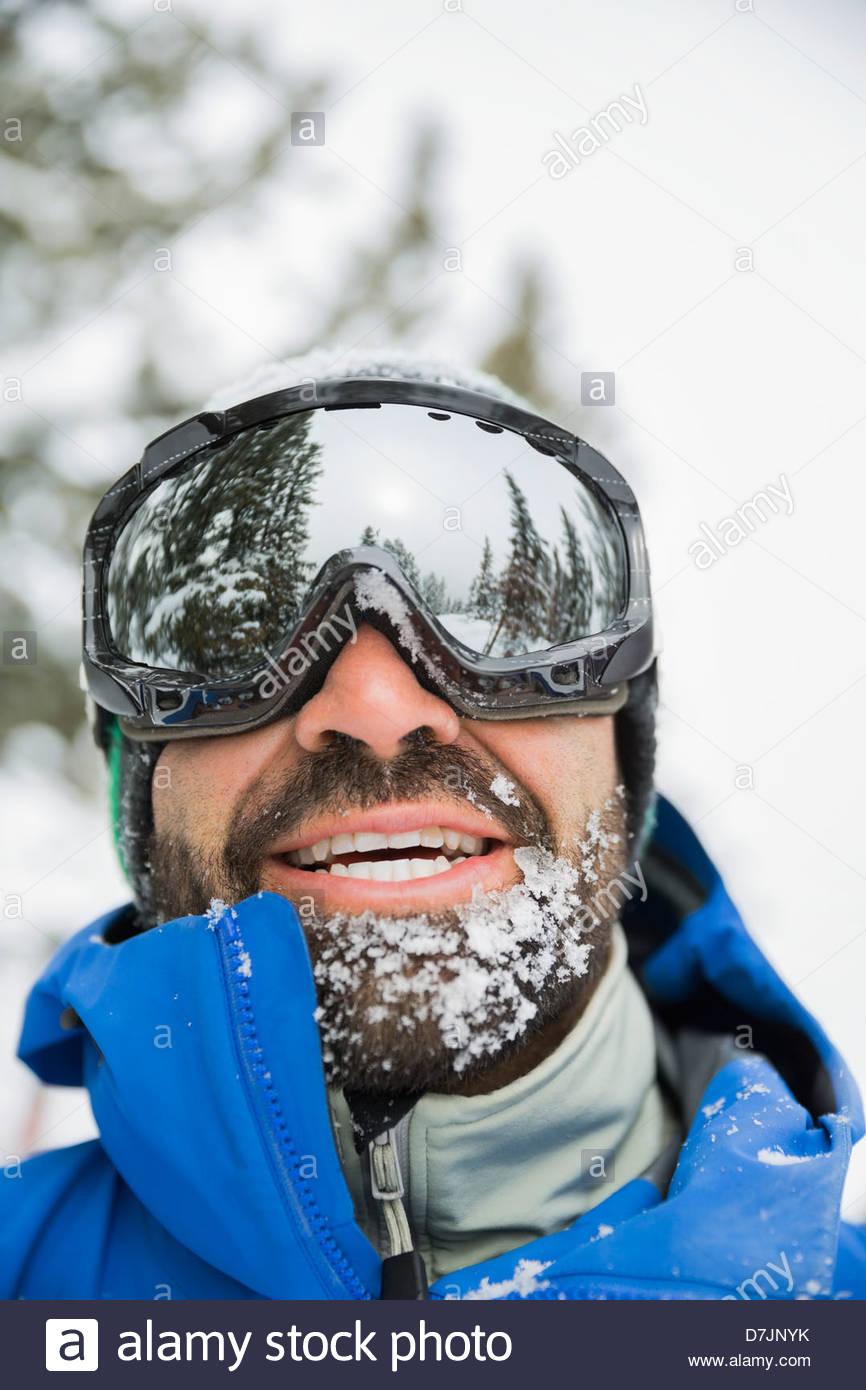 Smiling man wearing ski goggles in mountains - Stock Image