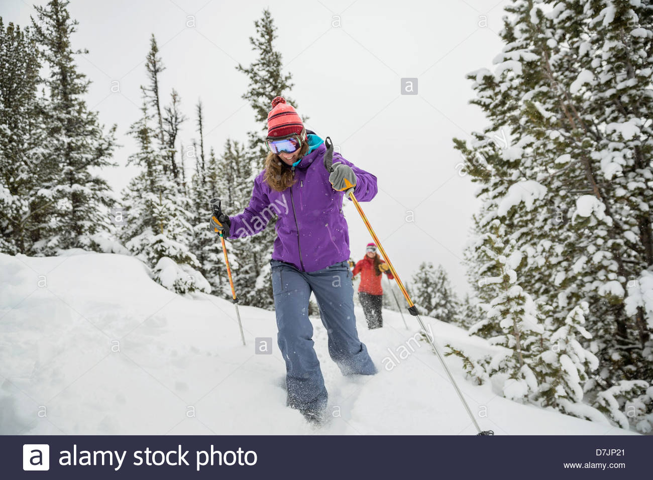 Women backcountry skiing in mountains - Stock Image