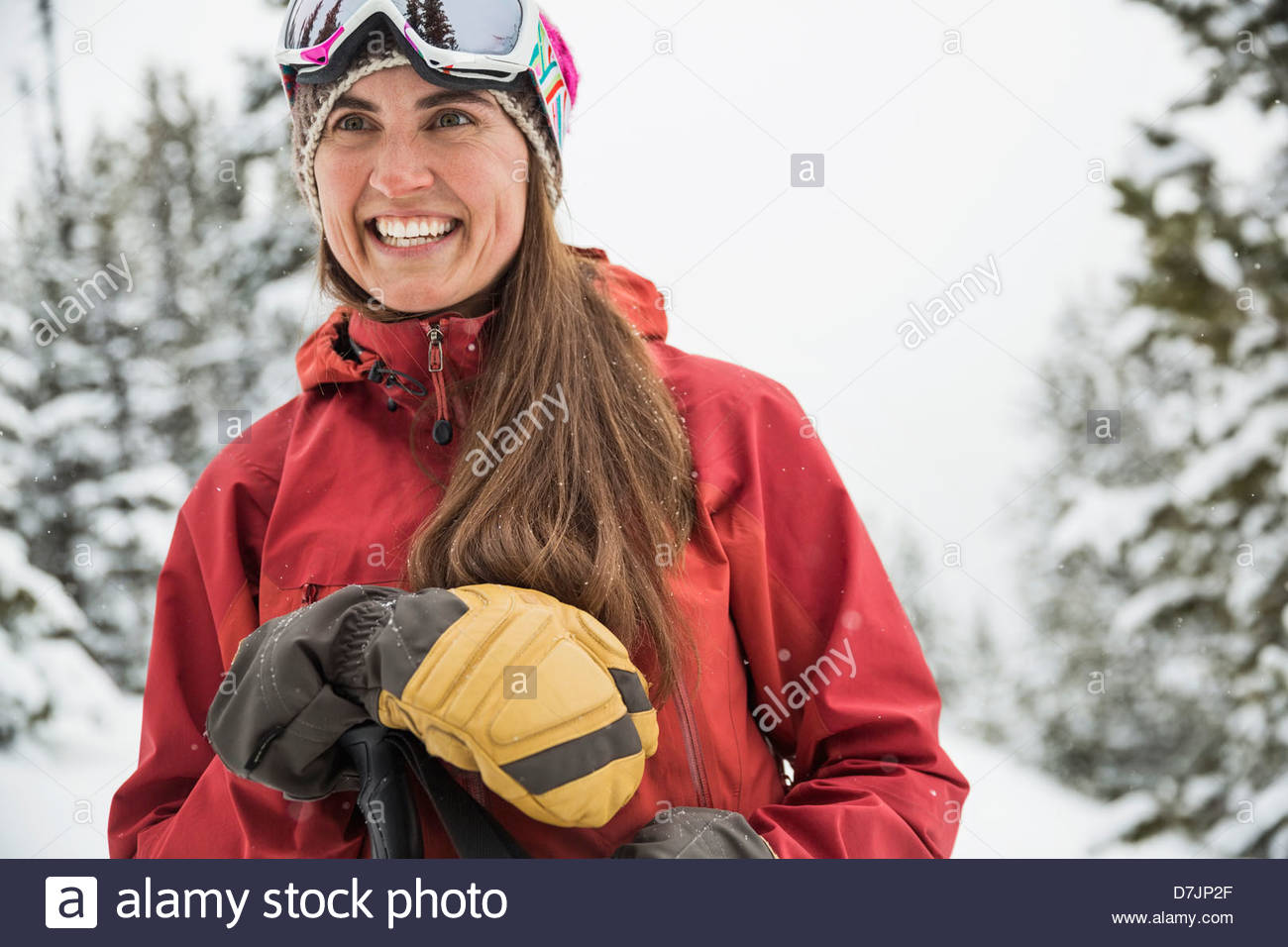 Smiling woman backcountry skiing in mountains - Stock Image