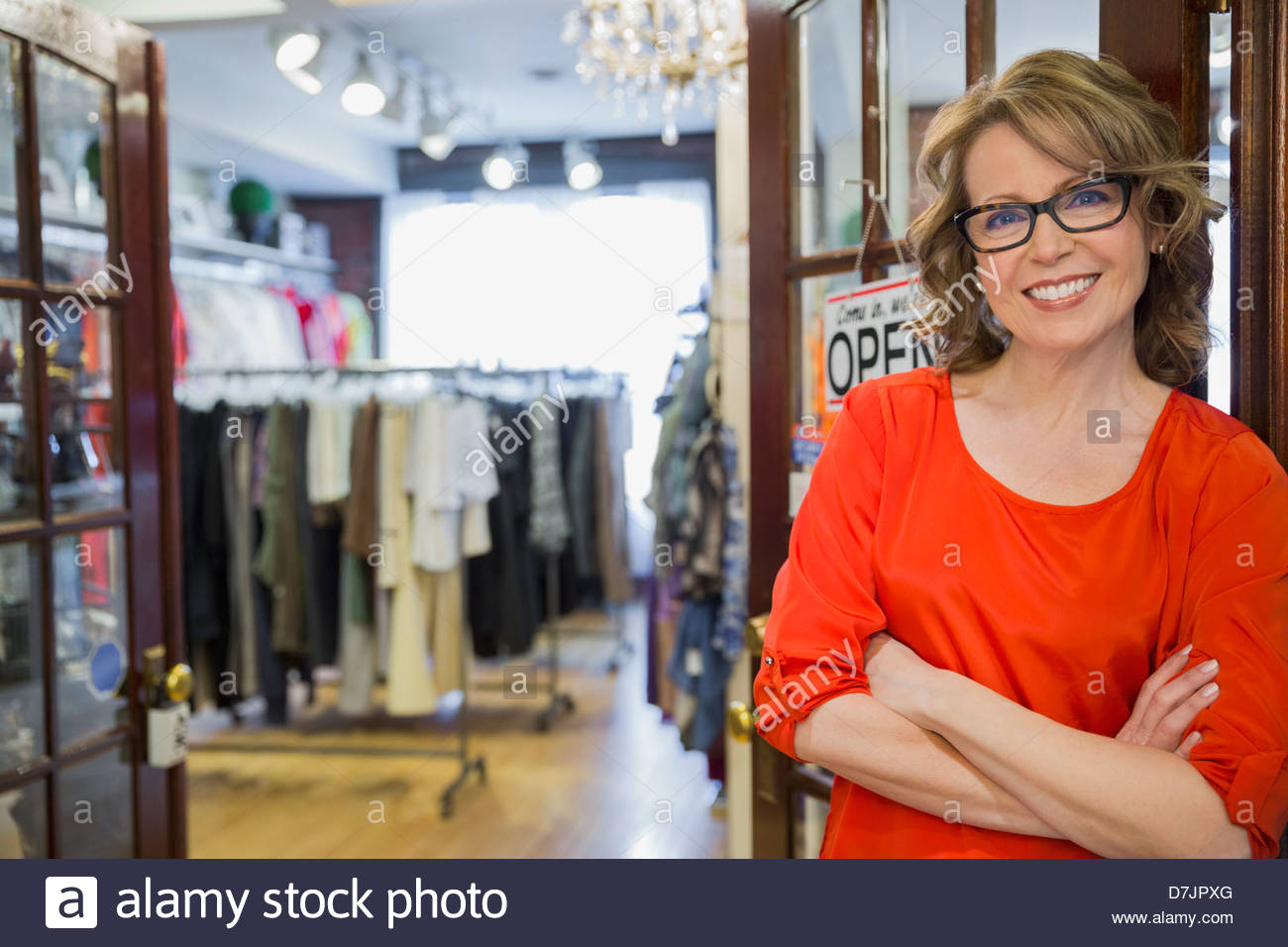 Portrait of female small business owner in store entrance - Stock Image