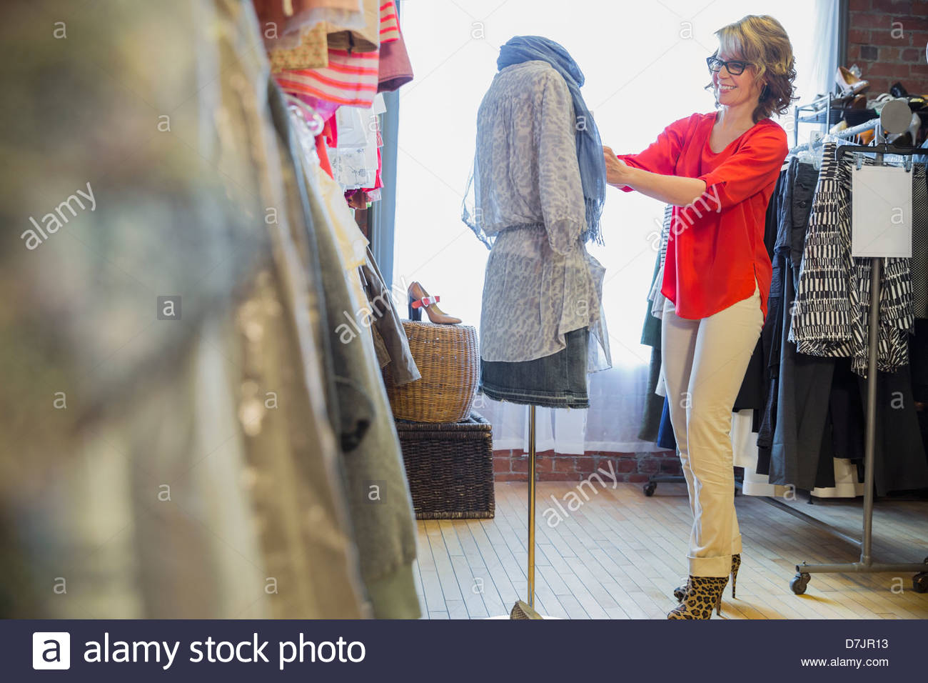 Female small business owner dressing mannequin in store - Stock Image