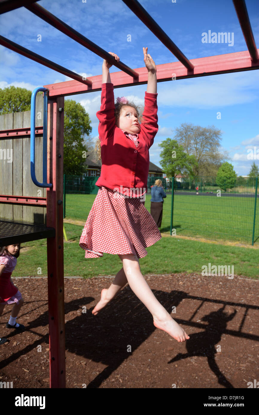A five year old girl in a school uniform plays on the monkey bars in the park after school - Stock Image