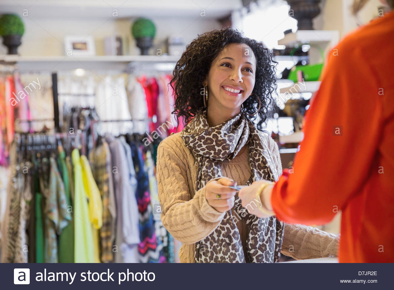 Female customer handing credit card to store owner for payment - Stock Image