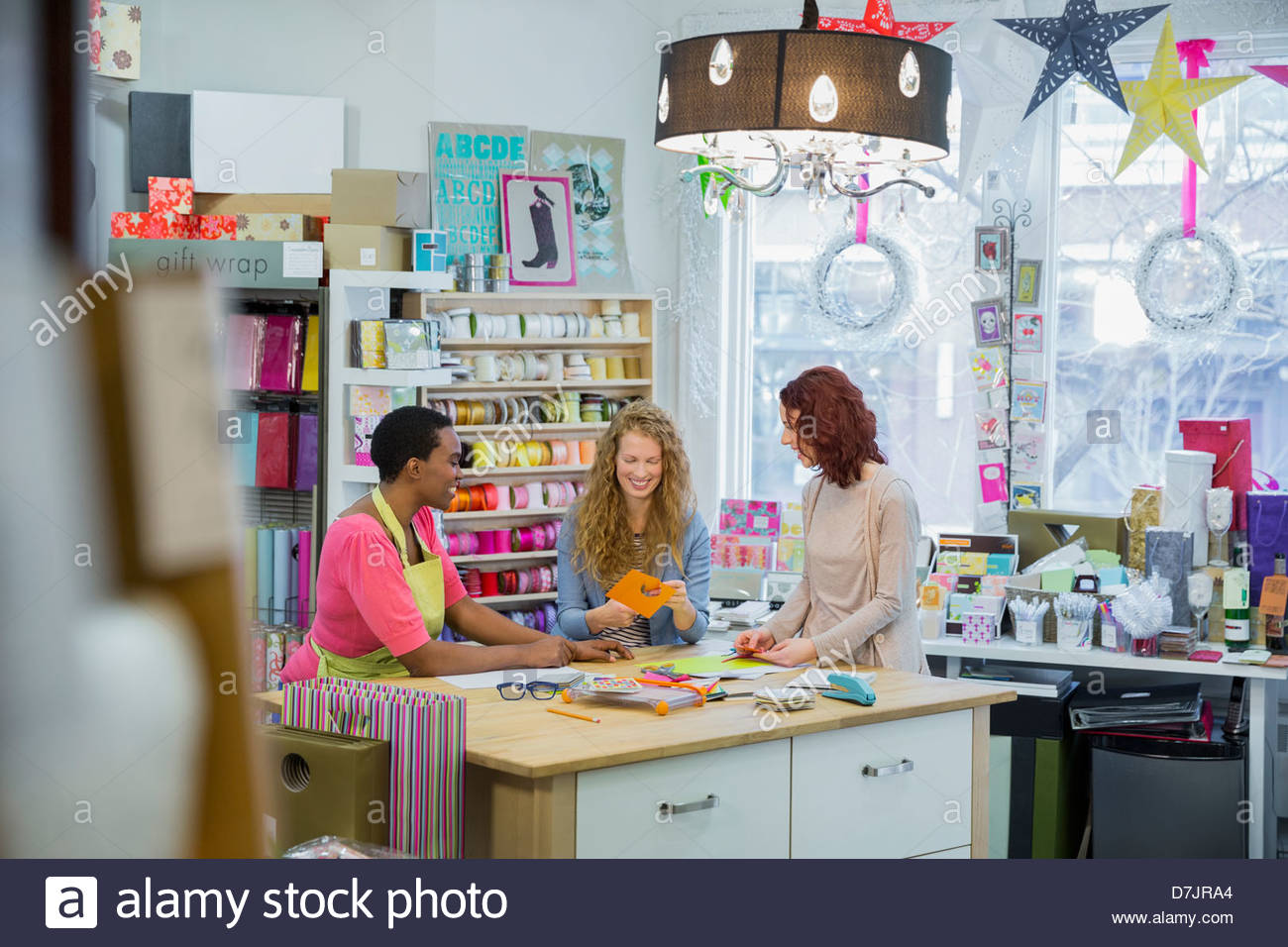 Female small business owner teaching customers in store - Stock Image