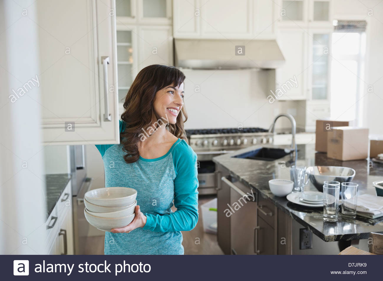 Woman putting away dishes in new home - Stock Image