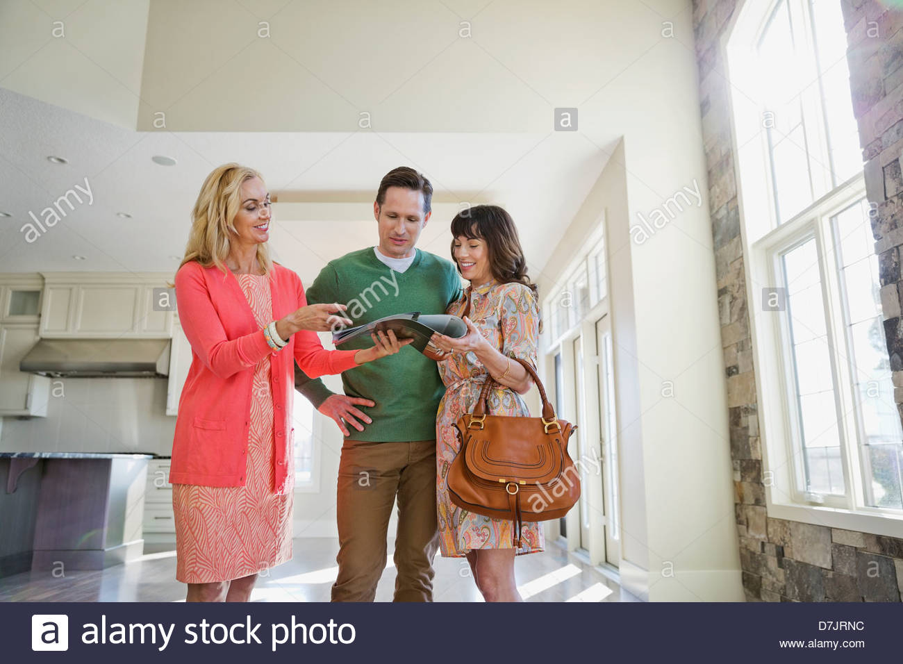 Female realtor showing brochure to couple in new home - Stock Image