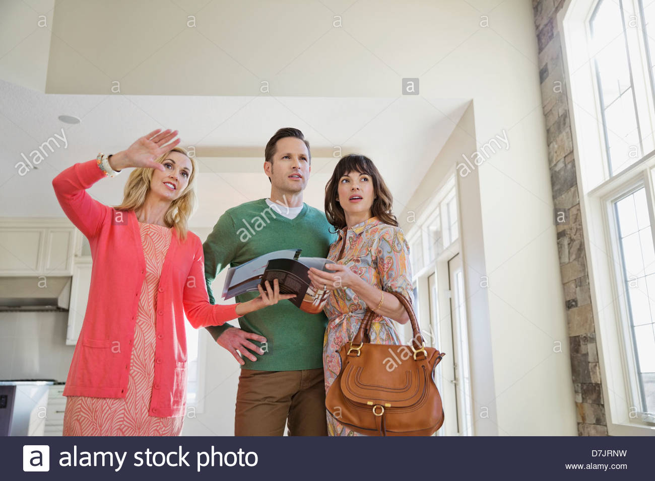 Female realtor showing new home to couple Stock Photo