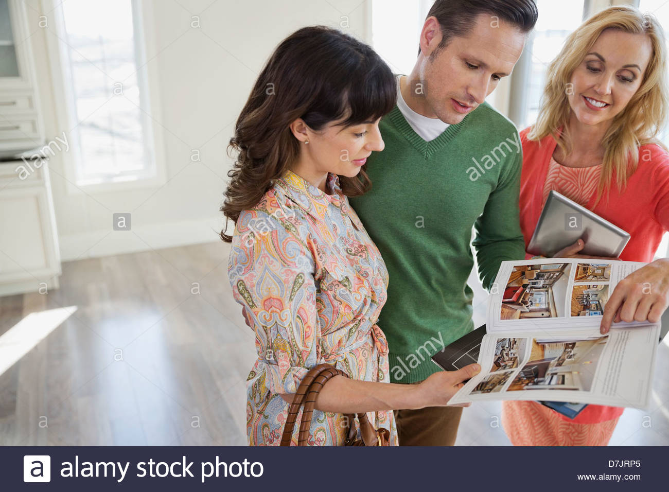 Female realtor showing new home brochure to couple Stock Photo