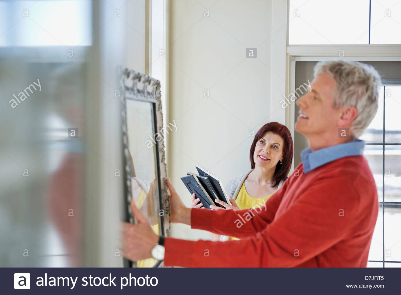 Mature couple hanging artwork in new home - Stock Image
