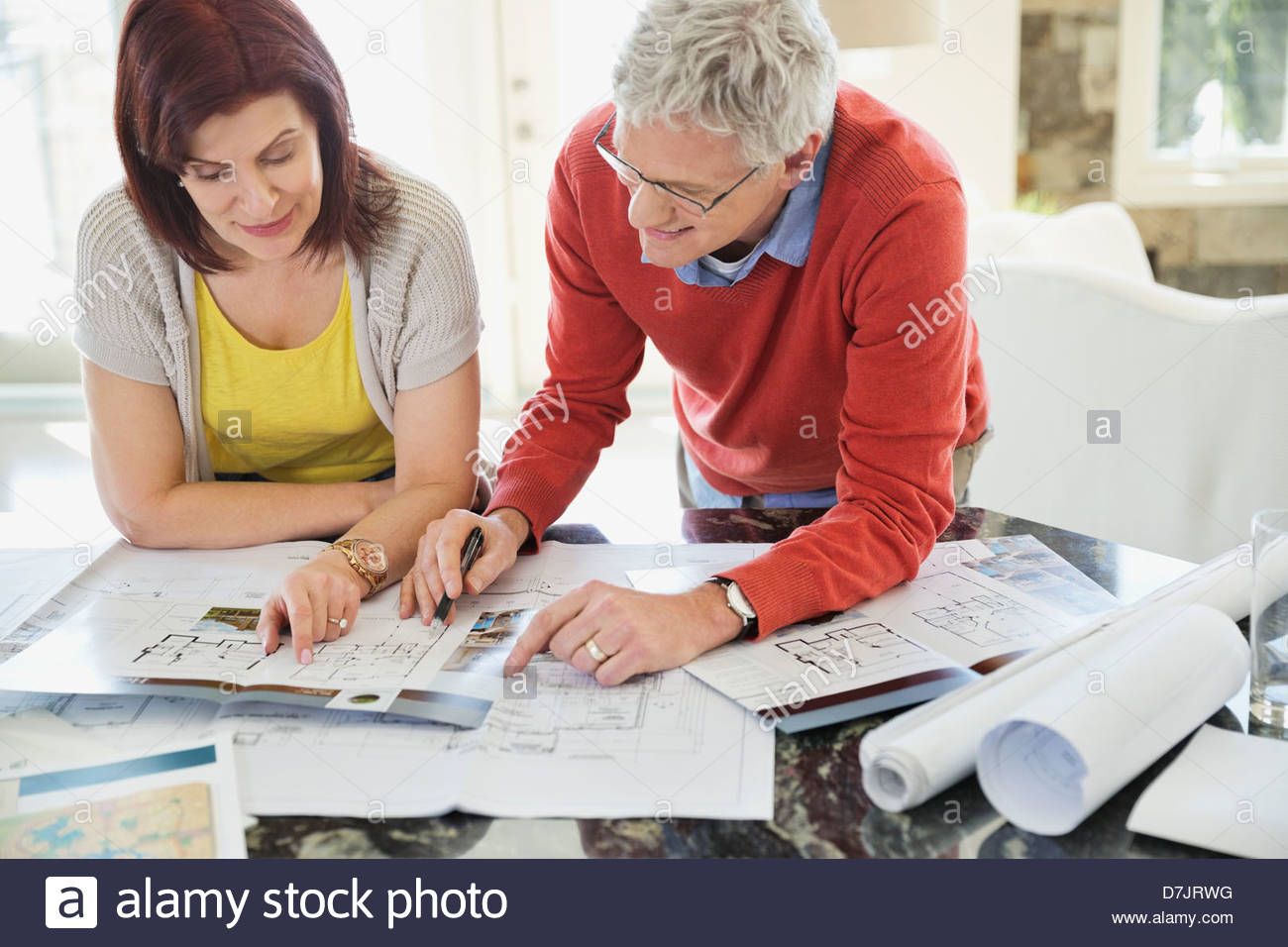 Mature couple discussing home designs in kitchen - Stock Image