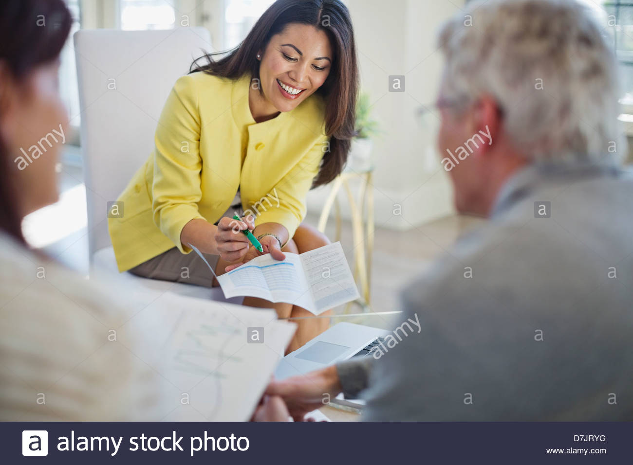 Female financial advisor working with couple in home - Stock Image
