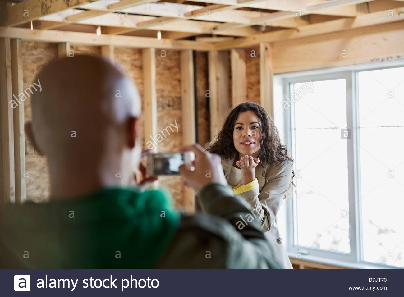 Young couple taking photographs in new home construction site Stock Photo