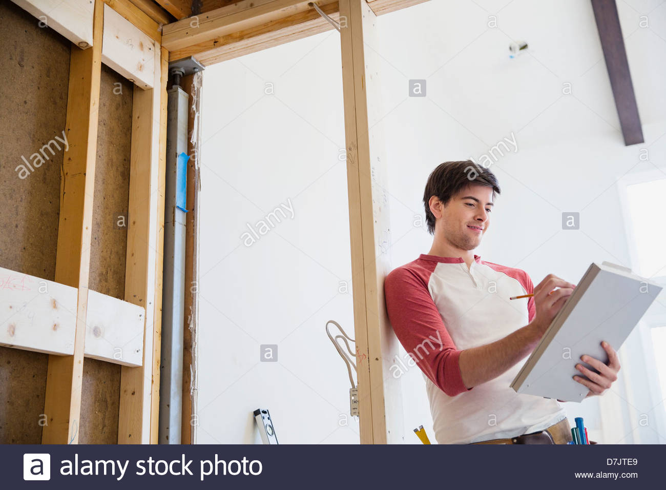 Man writing on clipboard in home - Stock Image