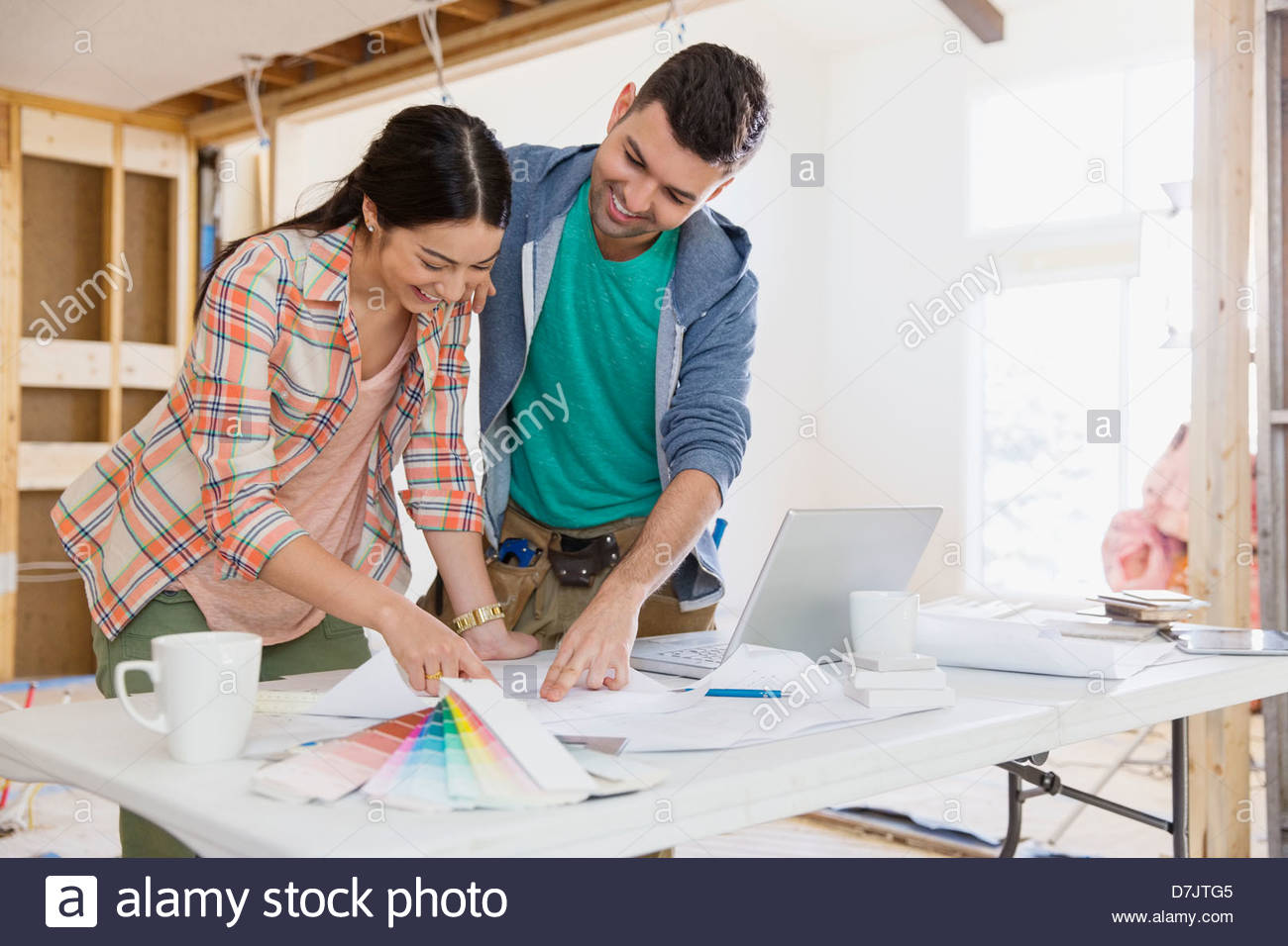 Couple discussing home designs in kitchen - Stock Image