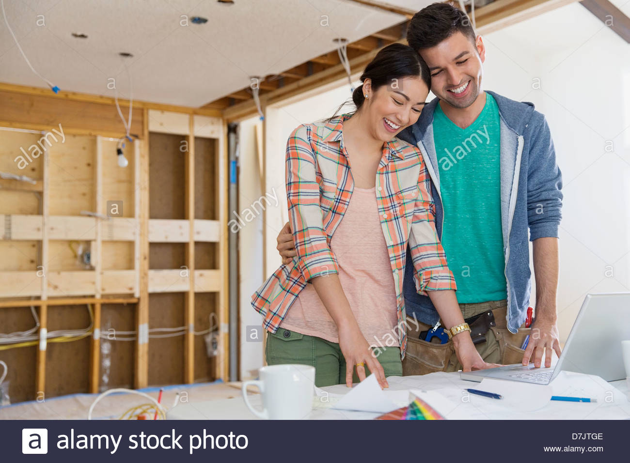 Couple with laptop discussing home designs in kitchen - Stock Image